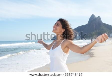 Latin woman at beach enjoying the air - stock photo