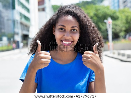 Latin woman with curly hair showing both thumbs - stock photo
