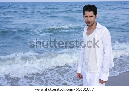Latin young man white shirt walking on blue beach outdoor - stock photo
