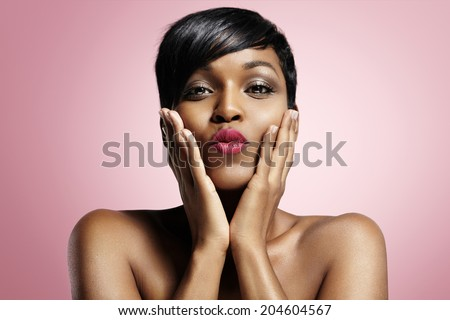 latina sending a kiss on a pink background - stock photo