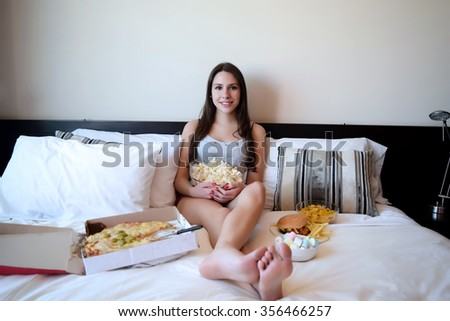 Latina woman in bed watching a movie or tv, and eating junk food.  - stock photo