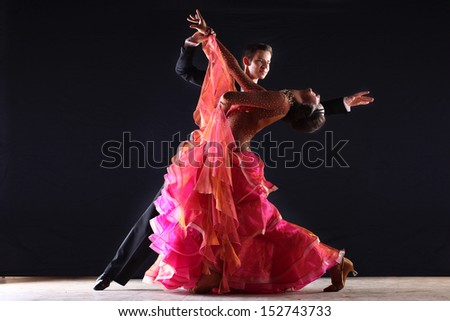Latino dancers in ballroom against black background - stock photo