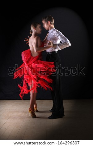 Latino dancers in ballroom against on black - stock photo