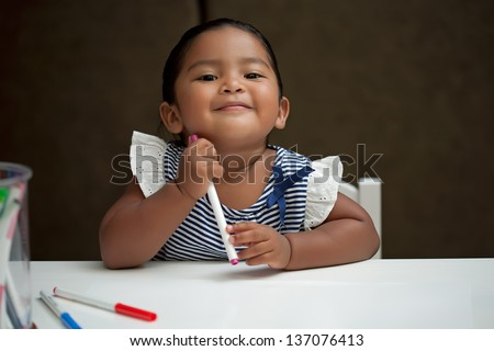 Latino girl holding a marker and smiling - stock photo