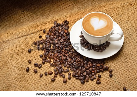 Latte art and coffee beans - stock photo
