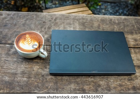 Latte art coffee cup with notebooks computer on wood desk view from above - stock photo
