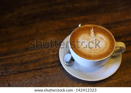 Latte art coffee over wooden background - stock photo