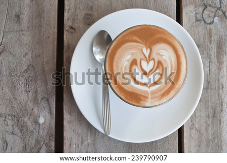 Latte art cup on wooden - stock photo