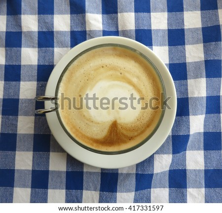 Latte in Italy on a blue checkered table  cloth                                 - stock photo