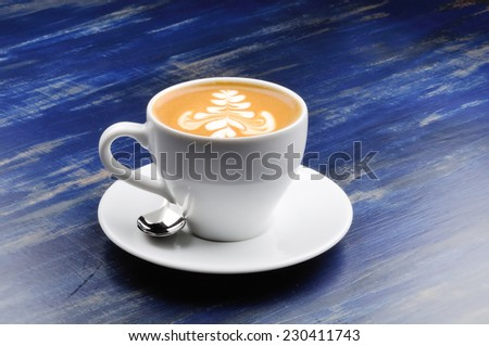 latte on a blue wood table - stock photo