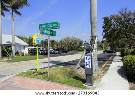LAUDERDALE-BY-THE-SEA, FL, USA - APRIL 7, 2014: Solar powered digital public parking meter and about fourteen parking spaces north of intersection of Commercial Blvd and E Tradewinds Ave.  - stock photo