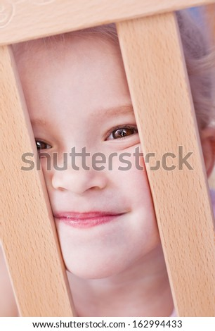 Laughing adorable little girl looking out of the crib - stock photo