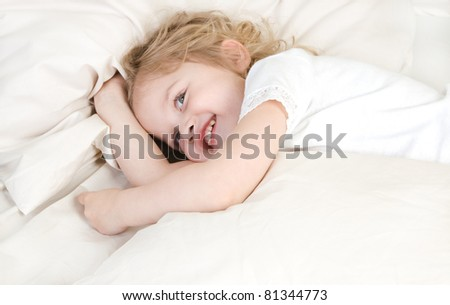 Laughing adorable little girl resting in the bed - stock photo