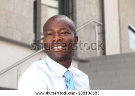 Laughing african businessman on stairs  - stock photo