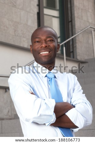 Laughing african businessman with crossed arms on stairs - stock photo
