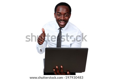 Laughing african man holding laptop and showing thumb up over white background - stock photo
