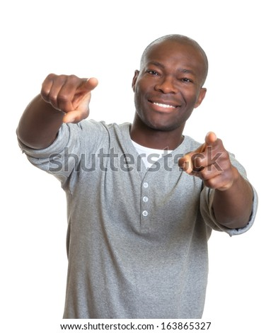 Laughing african man pointing with two fingers at camera - stock photo
