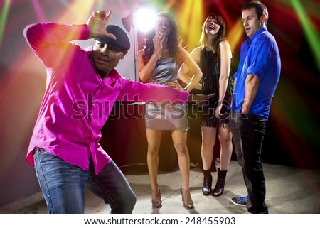 laughing at a man getting rejected by girls at a nightclub - stock photo