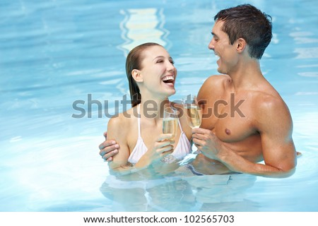 Laughing attractive happy couple with champagne wine in swimming pool - stock photo