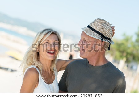 Laughing attractive middle-aged woman placing her trendy straw hat on her husbands head as they enjoy a day at the seaside - stock photo