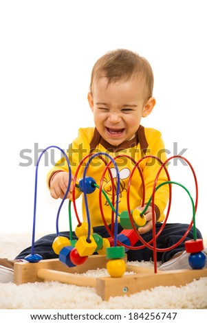Laughing baby boy having fun with wooden toy on fur carpet - stock photo