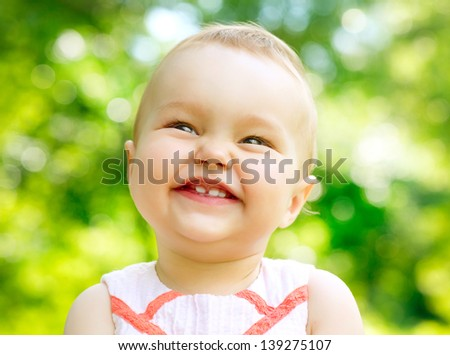 Laughing Baby Girl Portrait outdoor. Cute Child over nature background looking at camera - stock photo