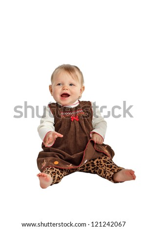 Laughing baby girl sits up. She has blue eyes, wispy hair, bare feet, and wears a brown velvet embroidered jumper with leopard print pants. Isolated/cut out on white background, vertical, copy space. - stock photo