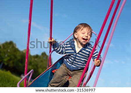 laughing baby on the swing - stock photo