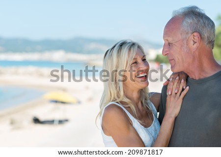 Laughing beautiful blond woman standing relaxing with her hands on her husbands shoulder looking into his eyes on a sunny tropical beachfront - stock photo