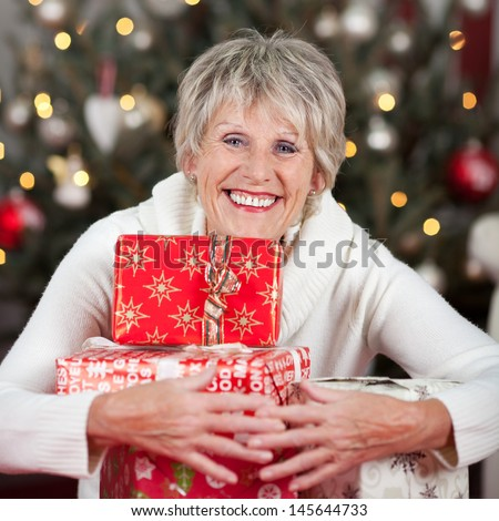 Laughing beautiful senior woman hugging a pile of Christmas gifts to her chest as she sits in front of a decorated Christmas tree - stock photo