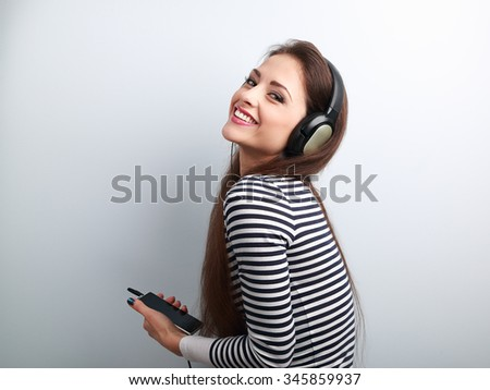 Laughing beautiful woman holding player and listening music in headphones on blue background - stock photo
