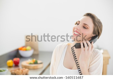 Laughing beautiful woman phoning with a telephone in her kitchen at home - stock photo