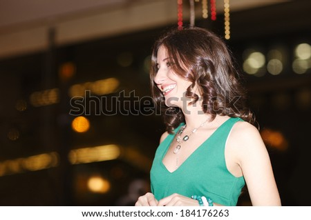 Laughing beautiful young woman in a nightclub enjoying a night out with friends, low angle close up view - stock photo
