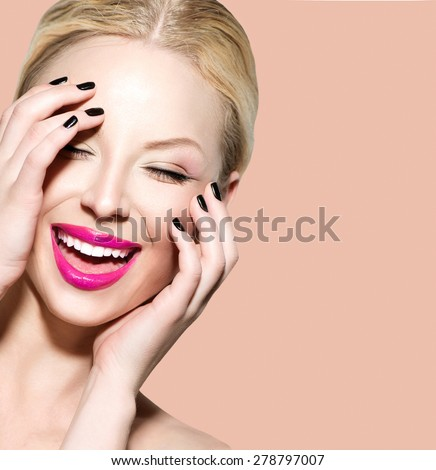 Laughing Beautiful Young Woman with Clean Fresh Skin close up over beige background. Beauty Portrait. Spa Woman Smiling and touching her skin. Perfect Fresh Skin. Model. Youth and Skin Care Concept - stock photo