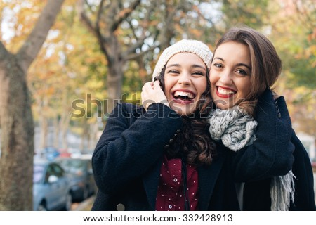Laughing best friends hugging outdoors in autumn - stock photo