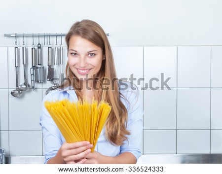 Laughing blonde woman with spaghetti at kitchen - stock photo