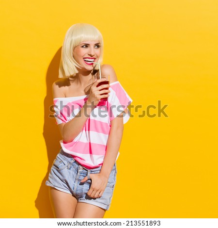 Laughing blonde young woman holding red drink and looking away. Three quarter length studio shot on yellow background. - stock photo