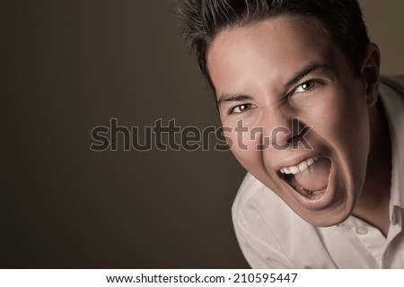 Laughing boy crying, shouting, screaming, hysteria on a brown background - stock photo