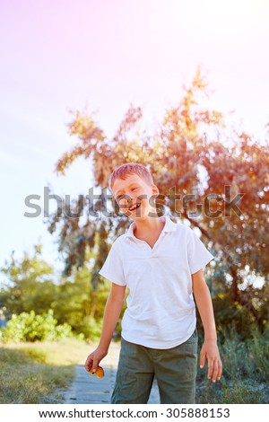 laughing boy looks into the camera in the outdoor over the blue sky - stock photo