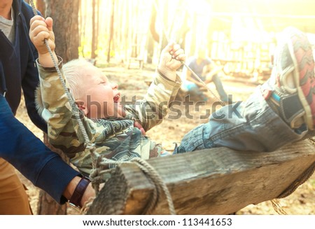 Laughing boy on swing - stock photo