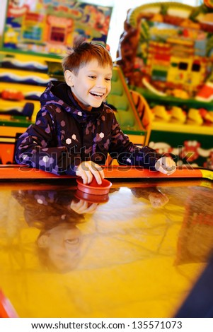 laughing boy playing air hockey game - stock photo