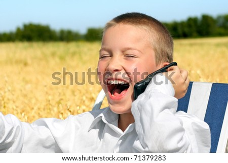 laughing boy with mobile phone in the field - stock photo