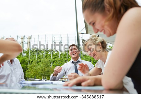 Laughing business people sitting on a table during a meeting outdoors - stock photo