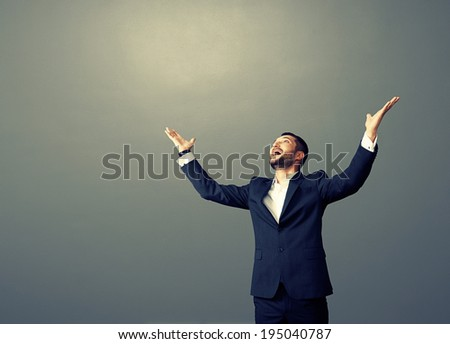 laughing businessman looking up over dark background - stock photo