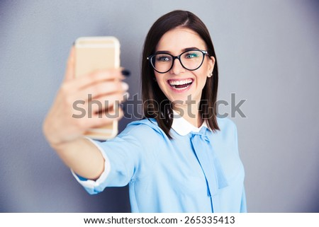Laughing businesswoman making selfie photo on smartphone. Wearing in blue shirt and glasses. Standing over gray background - stock photo