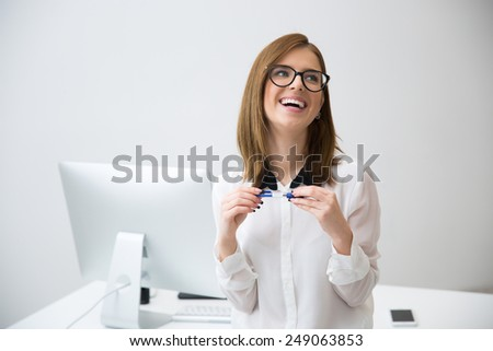Laughing businesswoman standing in office and looking away - stock photo