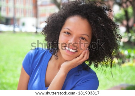 Laughing caribbean girl in a blue shirt  - stock photo