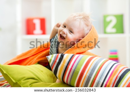 laughing child boy playing on pillows in bedroom - stock photo