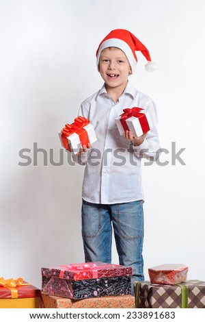 laughing child in Santa red hat holding Christmas gifts in hands. Christmas concept. - stock photo