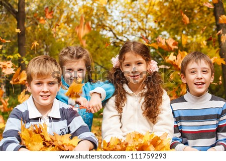Laughing children and yellow leaves falling on them - stock photo